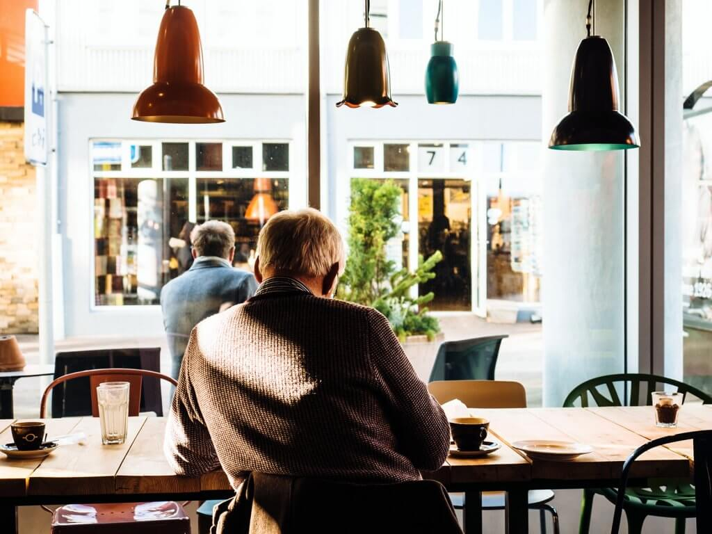 Photo of the back of a man reading in a cafe