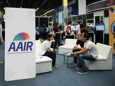 People at a conference with a banner displaying the AAIR logo