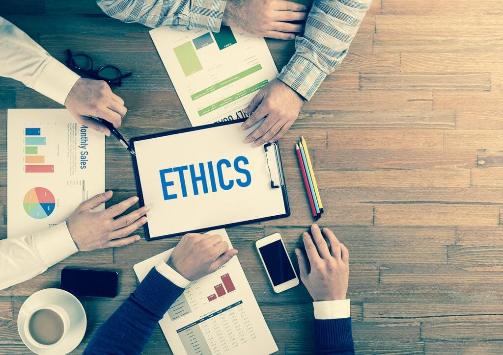 Photo of people's hands on a table looking at a clipboard with the word 'Ethics' on it
