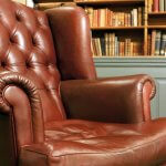 Photo of an old leather armchair in front of a bookcase