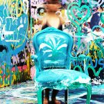 Artistic room with graffiti painted on all the walls and a brightly coloured antique chair in the middle of the room