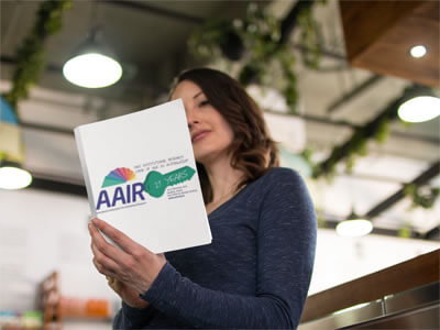 Photo of a woman reading a book with the AAIR Annual Forum 2010 logo on it