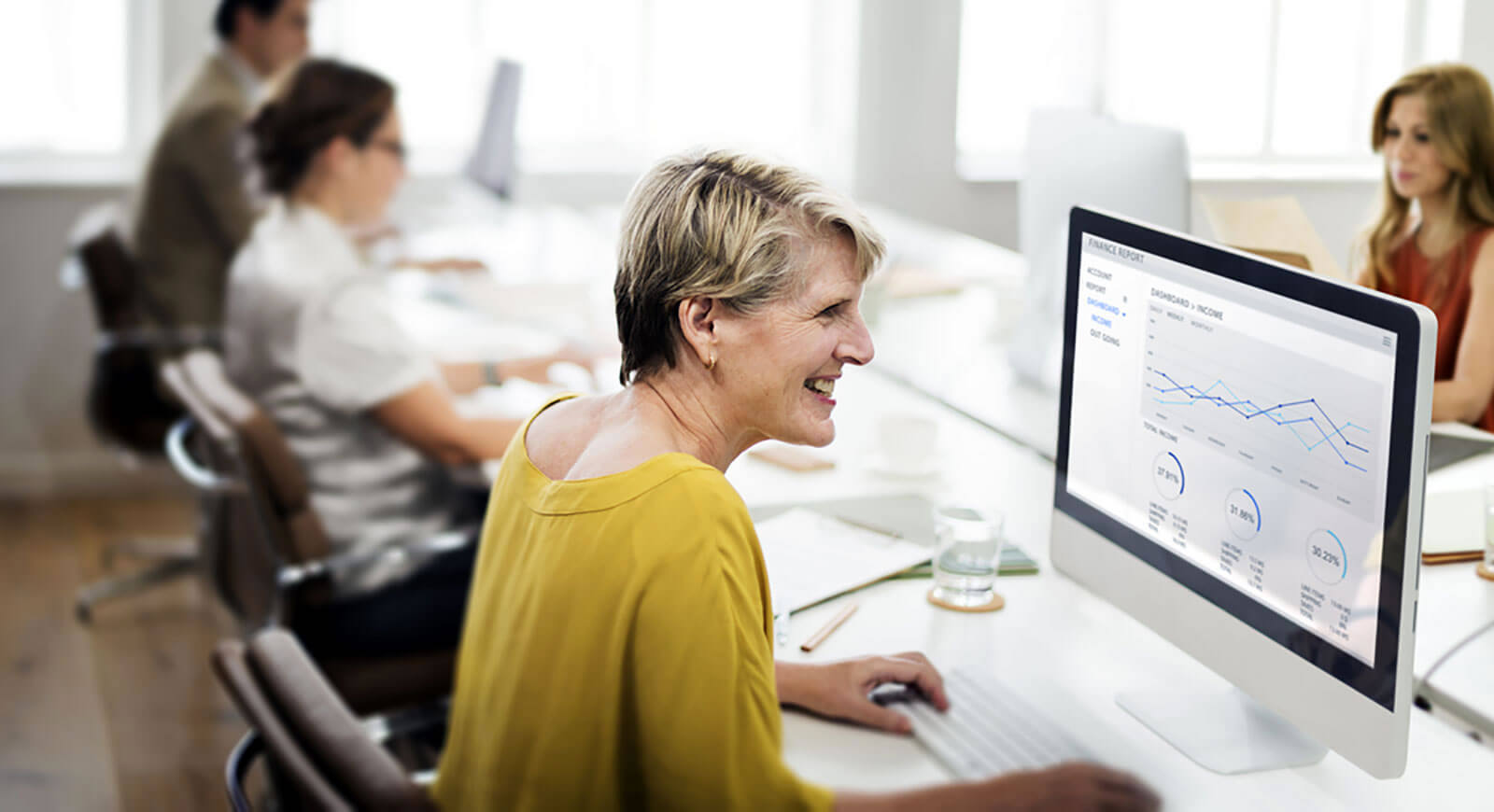 Photo of a lady at her desk looking at charts on her computer