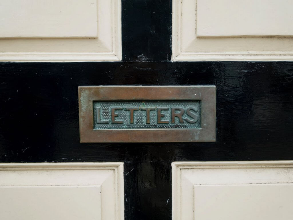 Photo of a letter slot in a door with the words LETTERS written on the slot