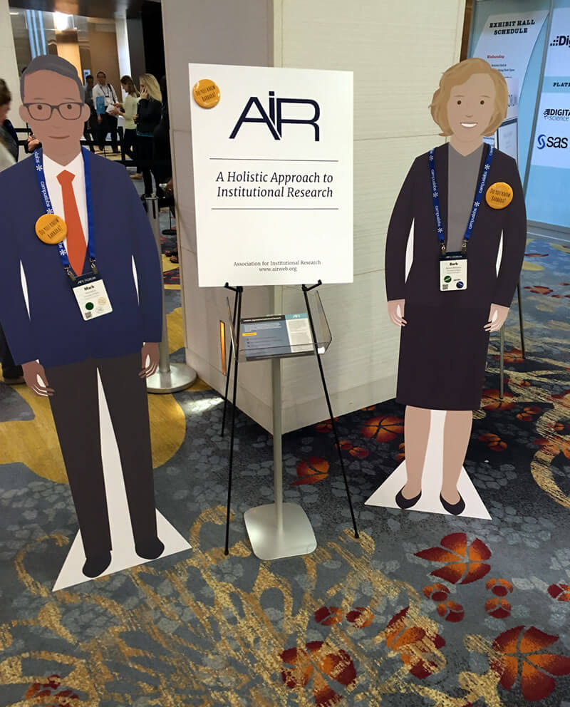 Photo of two cardboard cutout people advertising 'A Holistic Approach to Institutional Research'