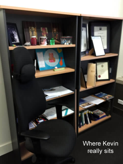 Photo of Kevin Maley's office chair with bookshelves in the background