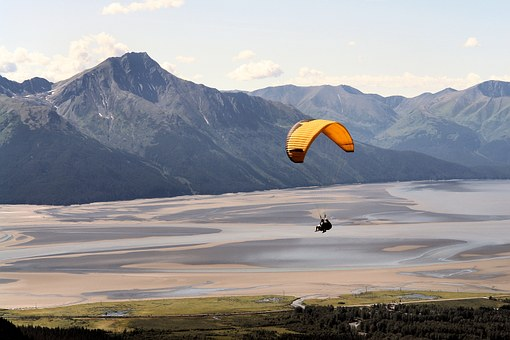 A person parasailing across forests and sands with mountains in the background