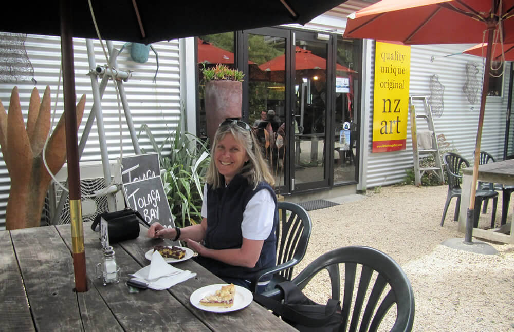 Photo of Louise Hargreaves eating cake in a cafe courtyard under a sun umbrella