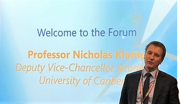 Photo of Professor Nicholas Klomp standing in front of a powerpoint screen
