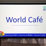 Photo of an overhead projector screen with the words 'World Cafe' on it