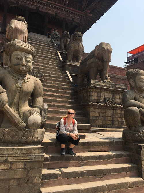 Photo of Liesha Northover sitting next to statues on the steps of an ancient building in Baktapur, Nepal