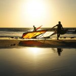Photograph of three windsurfers coming in from the sea with their boards at sunset