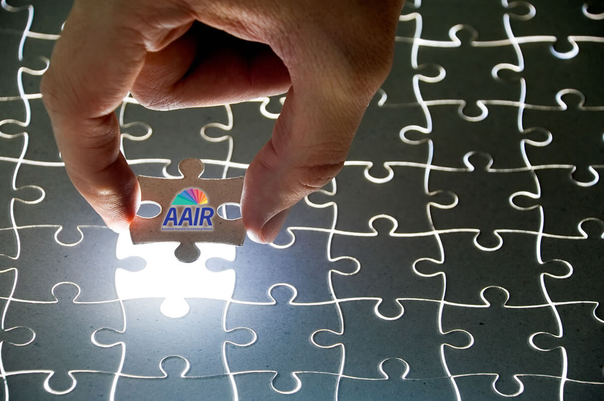 Photograph of a person's hand holding the last jigsaw puzzle piece with teh AAIR logo on it.