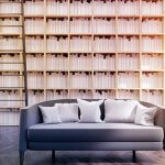Photo of a lounge chair in front of floor to ceiling bookcase
