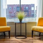 Photo of two yellow chairs and a coffee table in between with a plant on it and a building seen through a window behind