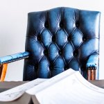 Photo of a blue leather studded desk chair behind a desk with a book on it
