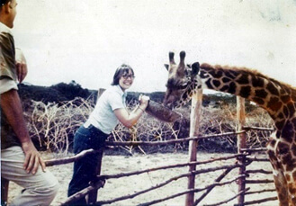 Photo of Kathie Rabel feeding a giraffe