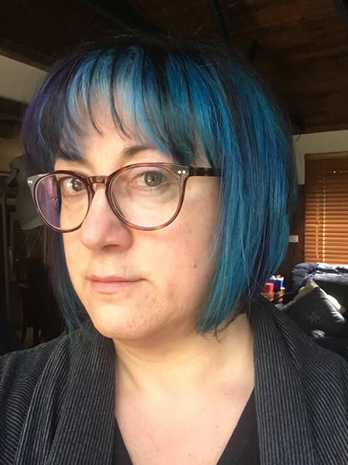 Photograph of Lisa Bolton with blue hair and wearing reading glasses