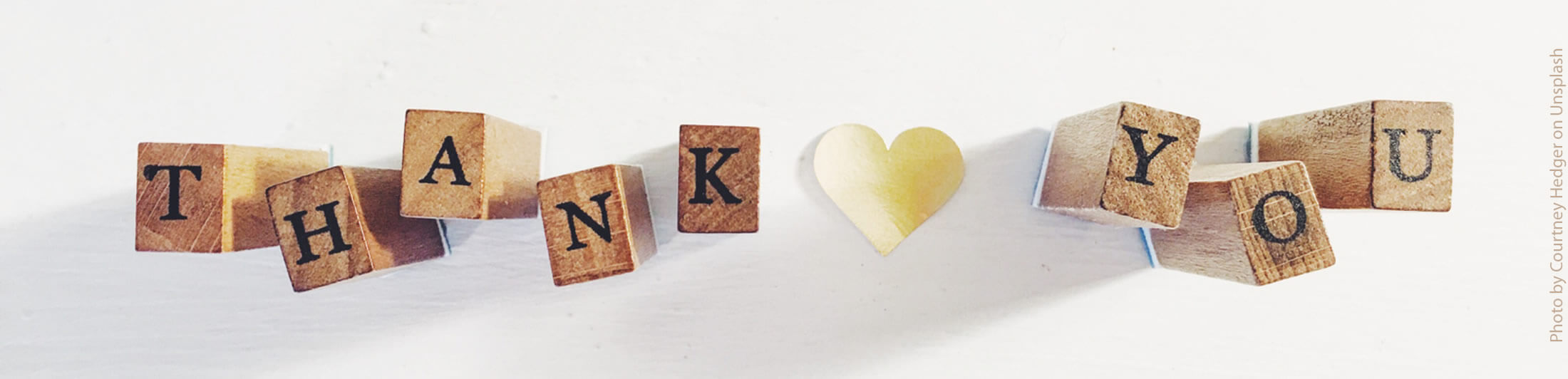 Wooden blocks with the letters THANK YOU with a gold heart in the middle