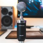 Picture of a microphone sitting on a desk with a speaker in the background