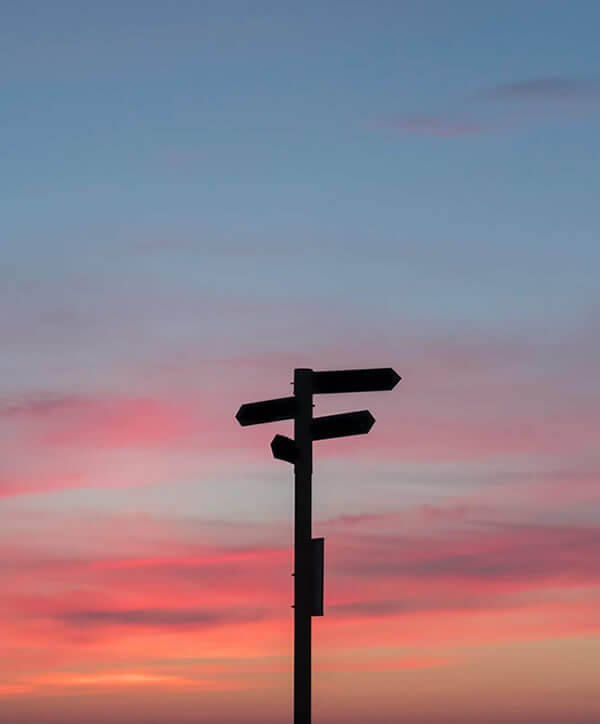 Photo of a sunset with the silhouette of a sign post with signs pointing in several directions