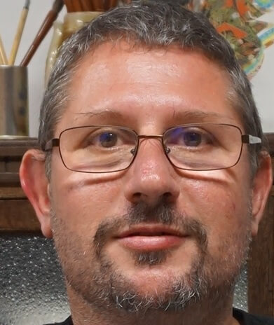 Close up photo of David Cawthorne wearing glasses and with a beard