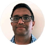 Photo of Anand Kulkarni wearing a blue and white checkered shirt and wearing glasses