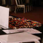 Photo of a conference table with laptop, papers and coloured lanyards