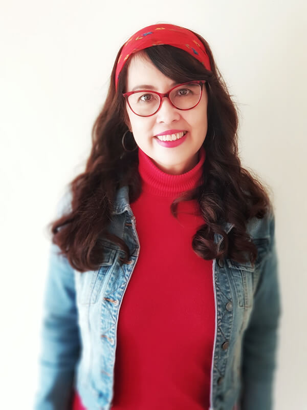 Photo of Grace Corpuz wearing a red top and headband, and a denim jacket and glasses.