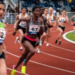 Photo of female athletes sprinting on a race track.