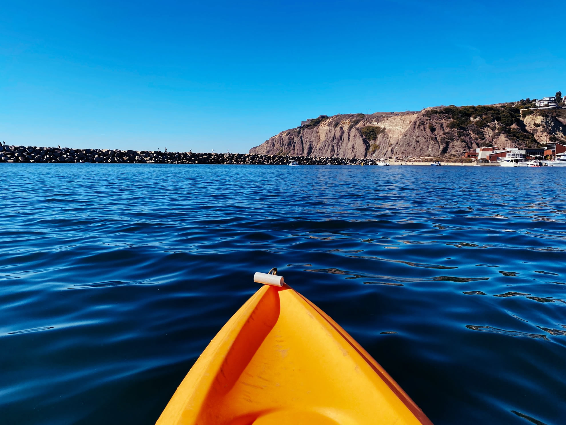 Photo of the front of an orange kayak on the ocean with a blue sky and rocks ahead