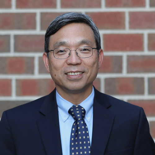 Photo of Henry Zheng wearing a suit and tie, glasses, and standing in front of a redbrick wall.