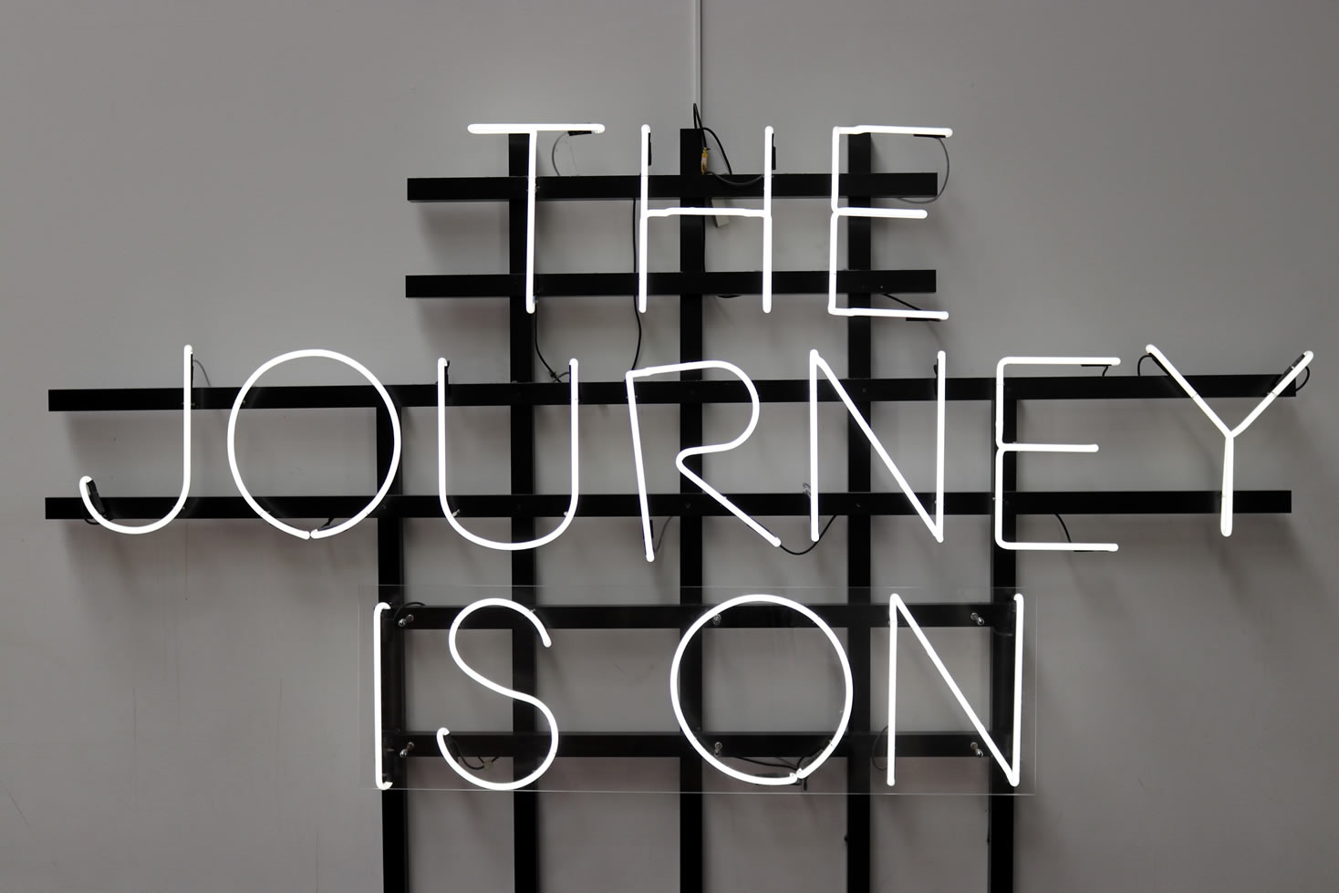 Photo of a neon sign (in black and white) reading, 'THE JOURNEY IS ON'.